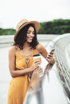 Mooie vrouw die van koffie en sociale media in openlucht geniet