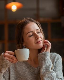 Mooie vrouw die van kop van koffie geniet