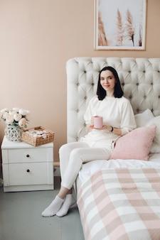 Mooie vrouw die van kop van ochtendthee of koffie in slaapkamer genieten.