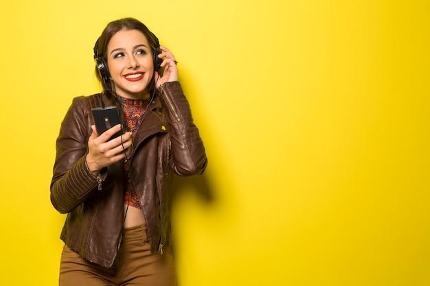 Mooie vrouw die van muziek met de hoofdtelefoons in gele muur geniet