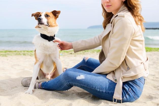 Mooie vrouw die van tijd in openlucht met haar hond geniet