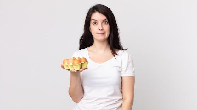 Mooie vrouw die verbaasd en verward kijkt en een eierdoos vasthoudt