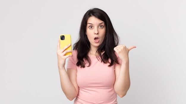 Mooie vrouw die verbaasd kijkt in ongeloof met behulp van een slimme telefoon