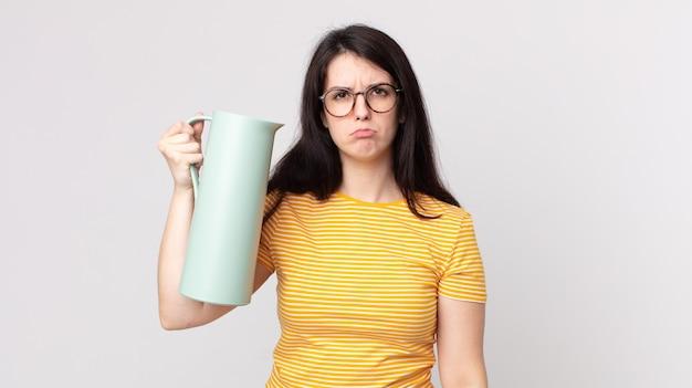 Mooie vrouw die verdrietig en zeurderig is met een ongelukkige blik en huilt en een koffiethermoskan vasthoudt