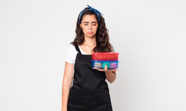 Mooie vrouw die verdrietig en zeurderig is met een ongelukkige blik en huilt en tupperwares met eten vasthoudt