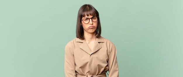 Mooie vrouw die verdrietig en zeurderig is met een ongelukkige blik, huilend met een negatieve en gefrustreerde houding