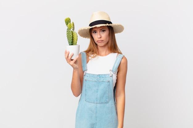 Mooie vrouw die verdrietig en zeurt met een ongelukkige blik en huilt en een decoratieve cactusplant vasthoudt