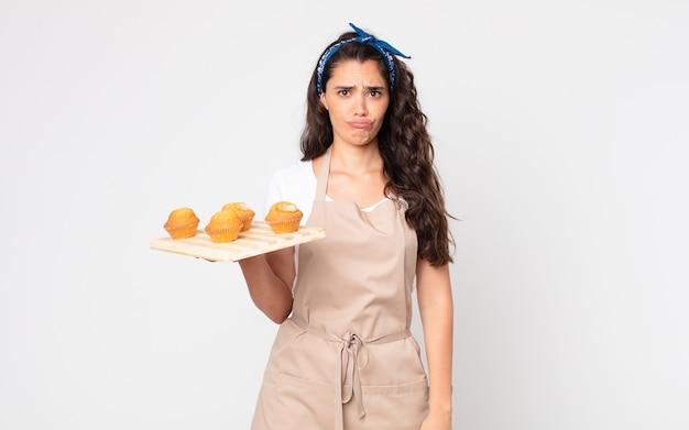 Mooie vrouw die verdrietig en zeurt met een ongelukkige blik en huilt en een dienblad met muffins vasthoudt