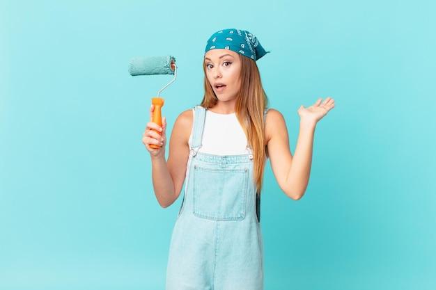 Mooie vrouw die verrast en geschokt kijkt, met open mond terwijl ze een object vasthoudt dat een nieuwe huismuur schildert