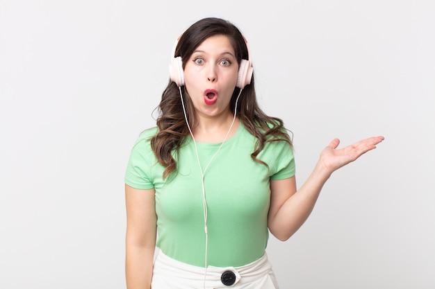 Mooie vrouw die verrast en geschokt kijkt, met open mond terwijl ze een object vasthoudt terwijl ze naar muziek luistert met een koptelefoon