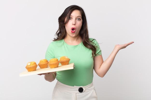 Mooie vrouw die verrast en geschokt kijkt, met open mond terwijl ze een voorwerp vasthoudt en een dienblad met muffins vasthoudt