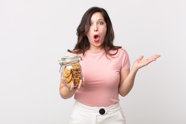 Mooie vrouw die verrast en geschokt kijkt, met open mond terwijl ze een voorwerp vasthoudt en een glazen fles met koekjes vasthoudt