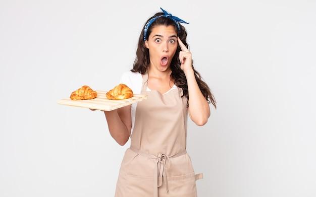 Mooie vrouw die verrast kijkt, een nieuwe gedachte, idee of concept realiseert en een dienblad met croissants vasthoudt