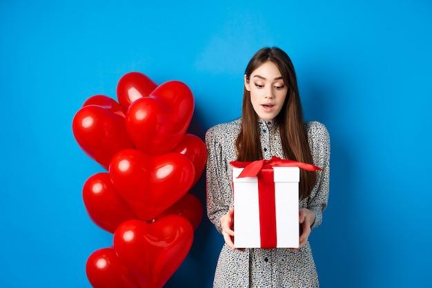 Mooie vrouw die verrast kijkt naar de geschenkdoos naast rode hartvormige ballonnen