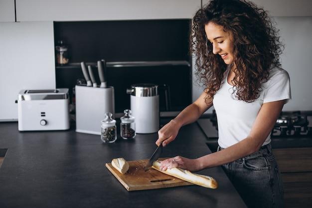 Mooie vrouw die vers brood eet bij de keuken