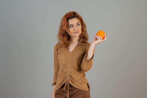 Mooie vrouw die verse sinaasappel houdt en weg kijkt.