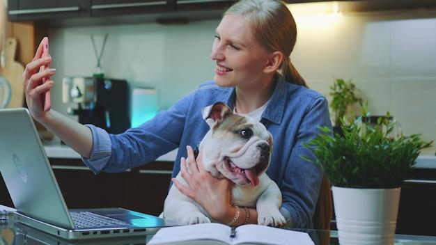 Mooie vrouw die video op smartphone met een kleine hond op haar handen telefoneert