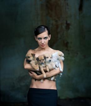 Mooie vrouw die vier puppy houdt.