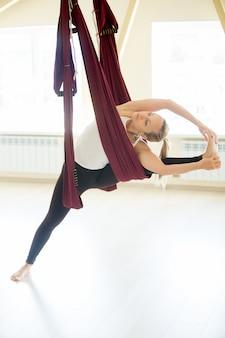 Mooie vrouw die visvamitrasana yoga doet in hangmat