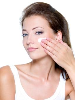Mooie vrouw die vochtinbrengende crème kosmetische room op gezicht toepast dat op wit wordt geïsoleerd