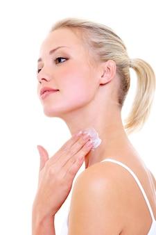 Mooie vrouw die vochtinbrengende crèmeroom op haar die hals toepast - op wit wordt geïsoleerd