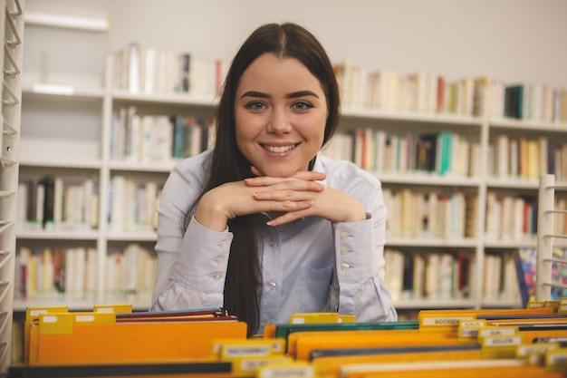 Mooie vrouw die voor boeken bij de opslag winkelt