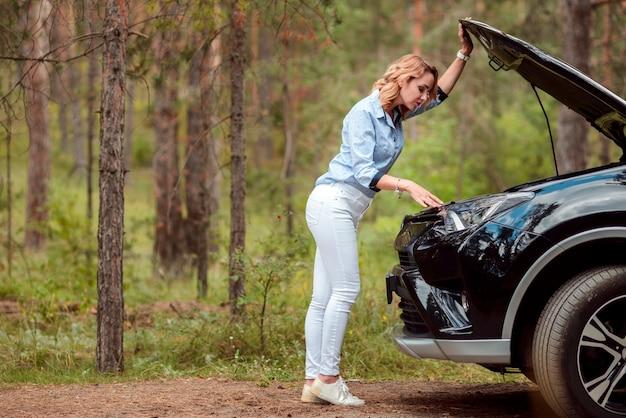 Mooie vrouw die voorzijde van auto controleert