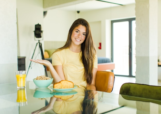 Mooie vrouw die vrolijk glimlacht, zich gelukkig voelt en een concept in exemplaarruimte met handpalm toont