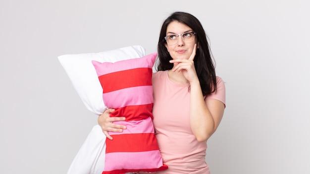 Mooie vrouw die vrolijk lacht en dagdroomt of twijfelt aan het dragen van een pyjama en een kussen vasthoudt