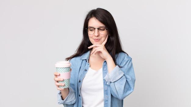 Mooie vrouw die vrolijk lacht en dagdroomt of twijfelt en een afhaalkoffie vasthoudt