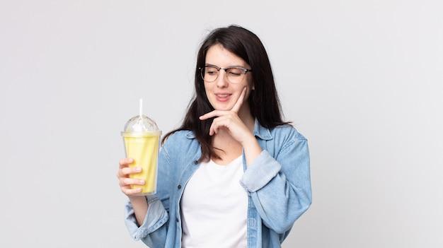 Mooie vrouw die vrolijk lacht en dagdroomt of twijfelt en een vanillemilkshake vasthoudt