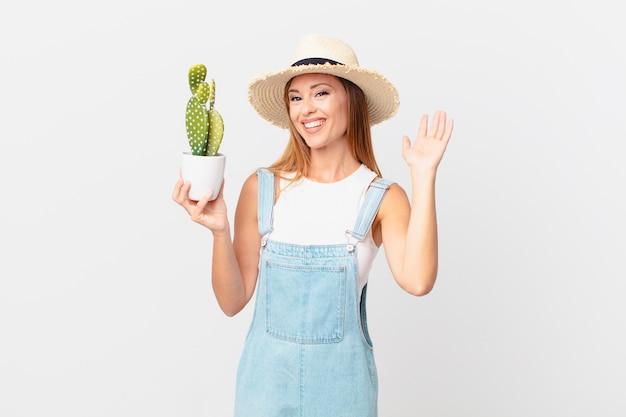 Mooie vrouw die vrolijk lacht, met de hand zwaait, je verwelkomt en begroet en een decoratieve cactusplant vasthoudt