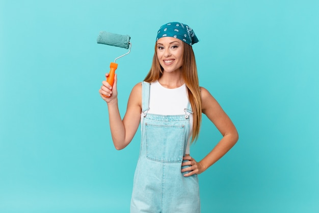 Mooie vrouw die vrolijk lacht met een hand op de heup en zelfverzekerd een nieuwe huismuur schildert