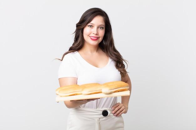 Mooie vrouw die vrolijk lacht met een hand op de heup en zelfverzekerd en een bakje met broodjes vasthoudt