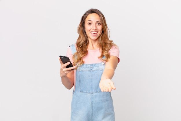 Mooie vrouw die vrolijk lacht met vriendelijk en een concept aanbiedt en toont en een smartphone vasthoudt