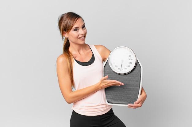 Mooie vrouw die vrolijk lacht, zich gelukkig voelt en een concept toont. dieet concept