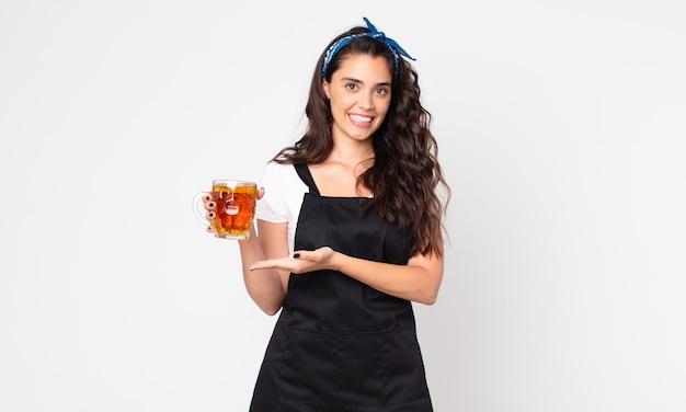 Mooie vrouw die vrolijk lacht, zich gelukkig voelt en een concept toont en een pint bier vasthoudt