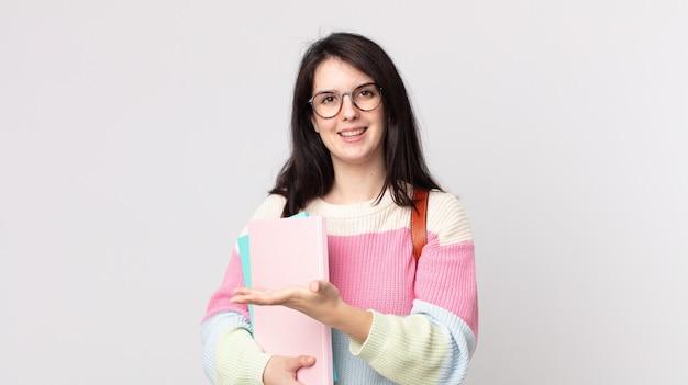 Mooie vrouw die vrolijk lacht, zich gelukkig voelt en een concept toont. universitair studentenconcept