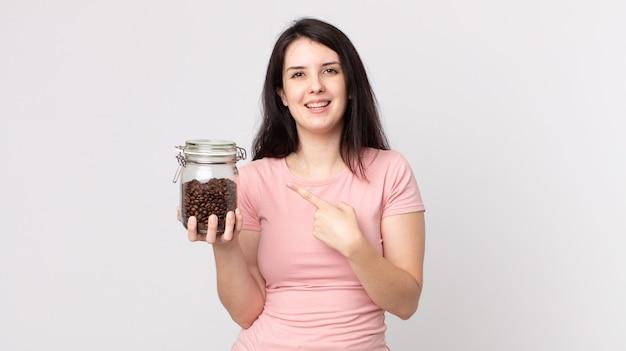 Mooie vrouw die vrolijk lacht, zich gelukkig voelt en naar de zijkant wijst en een fles koffiebonen vasthoudt
