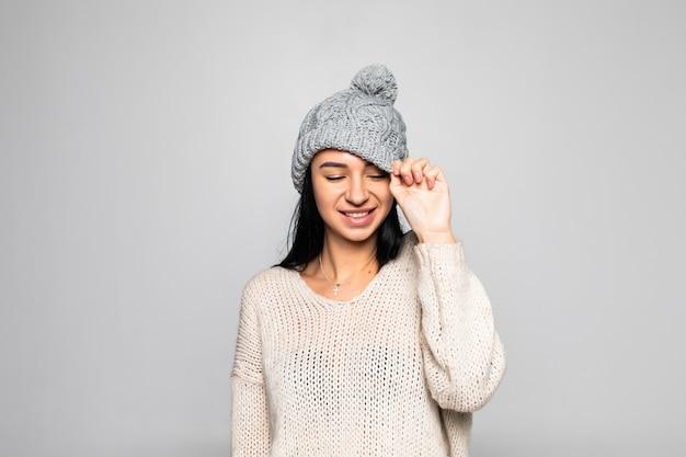Mooie vrouw die warme kleren, de winterportret draagt dat op grijze muur wordt geïsoleerd.