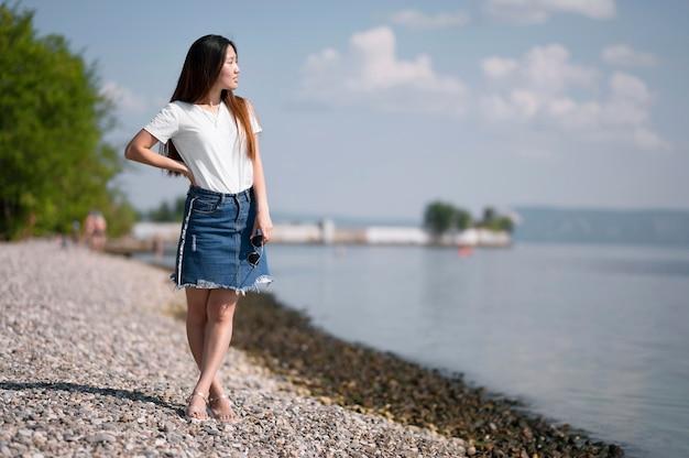 Mooie vrouw die weg op het strand met exemplaarruimte kijkt