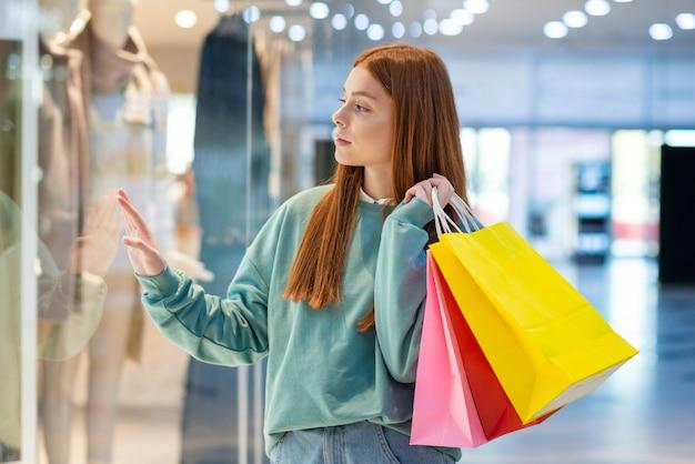 Mooie vrouw die winkelvenster bekijkt