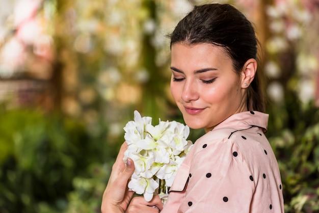 Mooie vrouw die witte bloem in groen huis ruikt