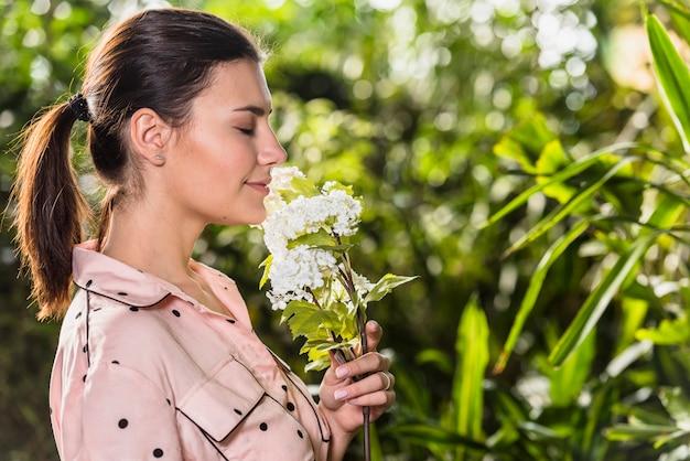 Mooie vrouw die witte bloemen ruikt