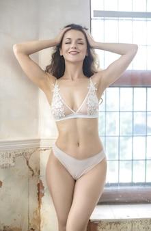 Mooie vrouw die witte elegante lingerie draagt