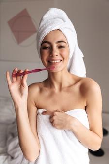 Mooie vrouw die witte handdoek draagt die zich in badkamers bevindt, en tanden met borstel schoonmaakt