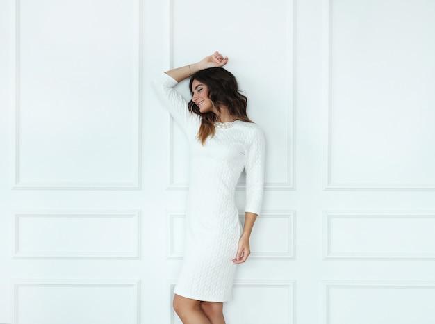 Mooie vrouw die witte kleding in witte ruimte draagt