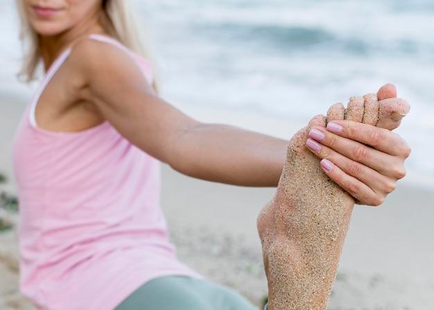 Mooie vrouw die yoga beoefent op het strand