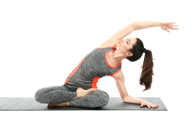 Mooie vrouw die yoga beoefent op wit