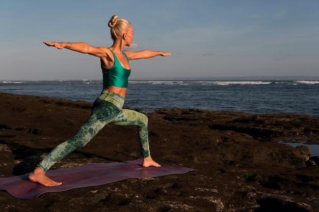 Mooie vrouw die yoga doet. middelste plan